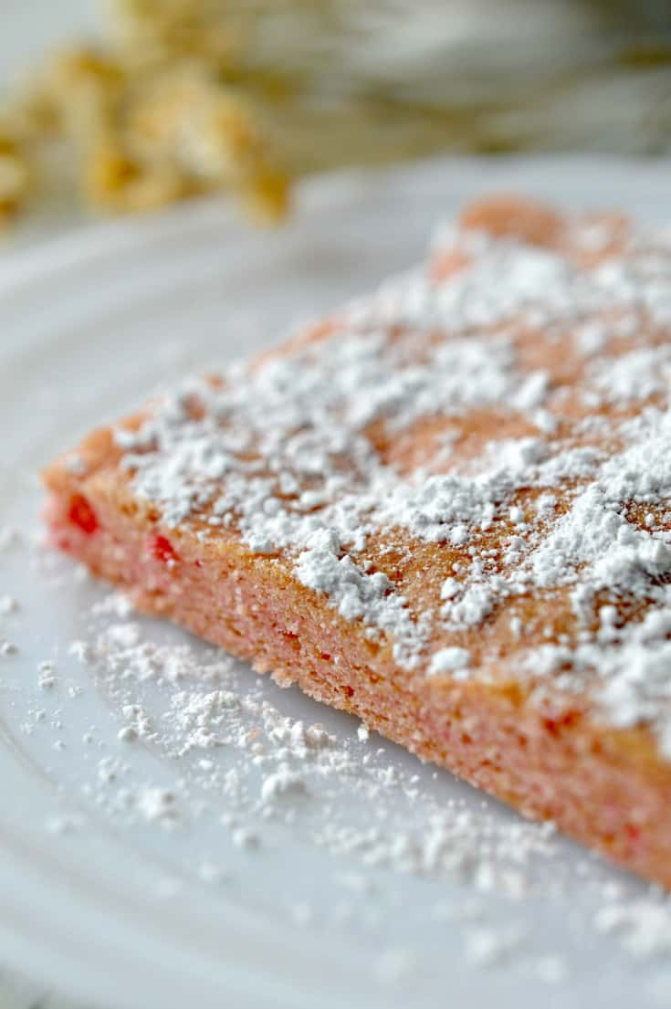 Strawberry Cake Mix Brownies with powder sugar topping on a plate